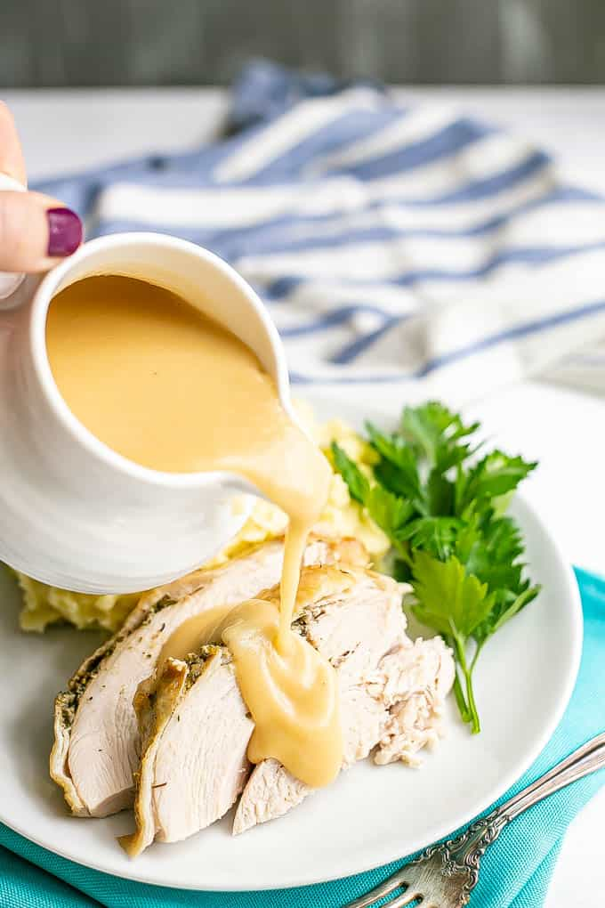 Gravy being poured from a white gravy dish over sliced turkey breast on a white dinner plate