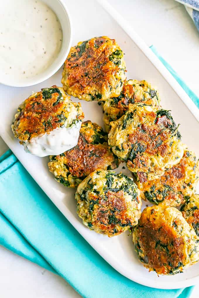Crispy baked spinach cheese bacon cakes on a white serving platter with a bowl of Ranch dressing