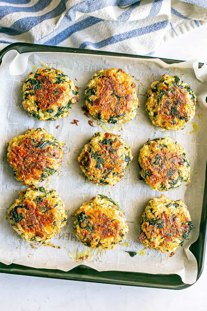 Crispy spinach cakes with cheddar and bacon on a small baking tray lined with parchment paper after baking