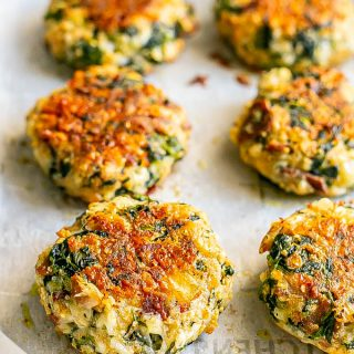 Baked golden brown cheesy spinach cakes with bacon on parchment paper on a baking pan