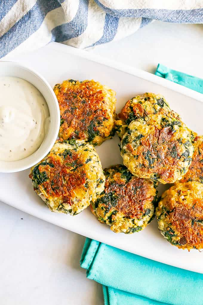 Golden brown spinach cheddar bacon cakes on a white serving platter with a bowl of Ranch dressing