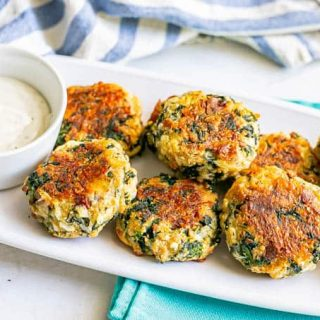 Crispy baked spinach cheese bacon cakes piled up on a white serving platter with a bowl of Ranch dressing