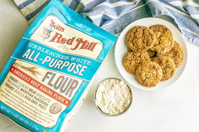 A plate of cookies next to Bob's Red Mill all purpose flour and a cup full of measured flour