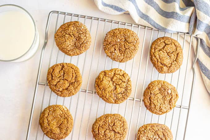 Ginger snaps on a cooling rack with a glass of milk nearby