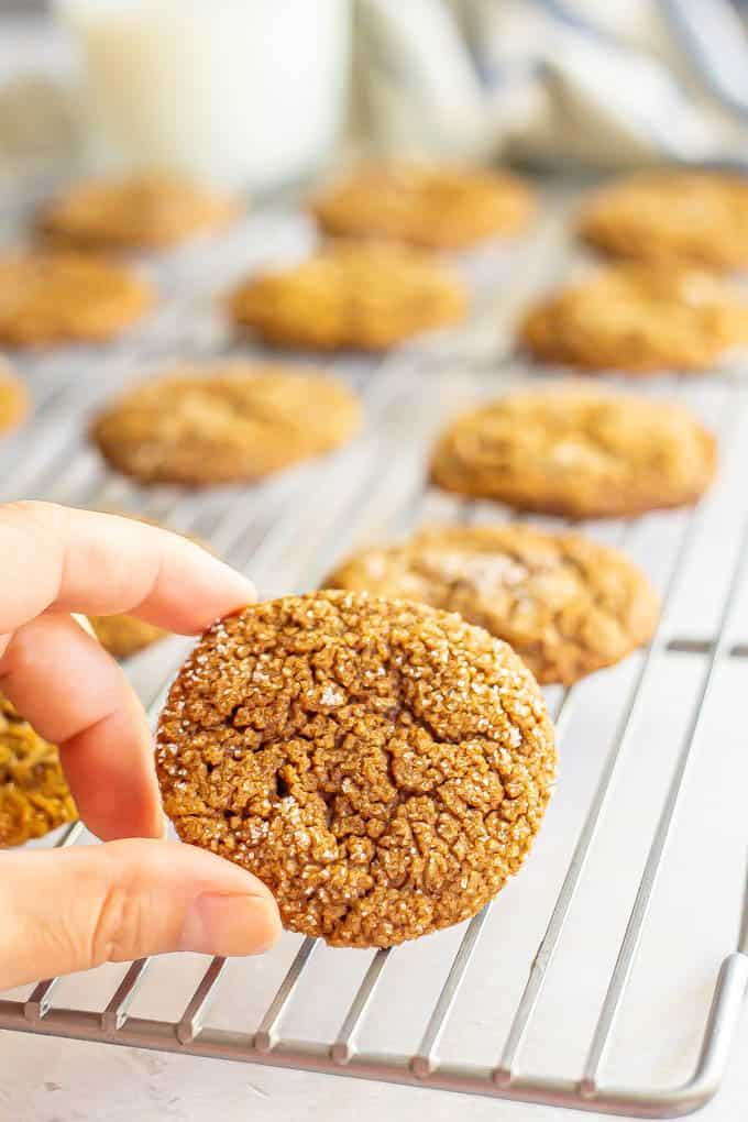 A hand picking up a small ginger cookie from a cooling rack