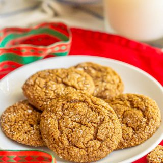 A plate of sugar sprinkled ginger snap cookies and a Christmas ribbon nearby
