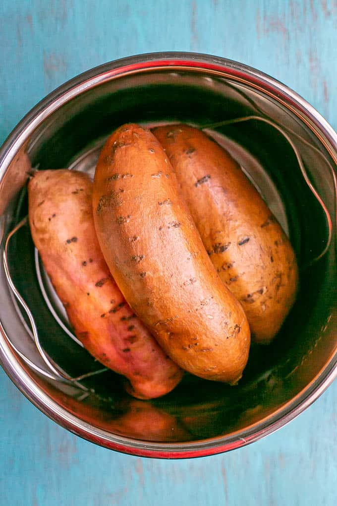 Three sweet potatoes placed on a trivet in the insert of an Instant Pot before being cooked