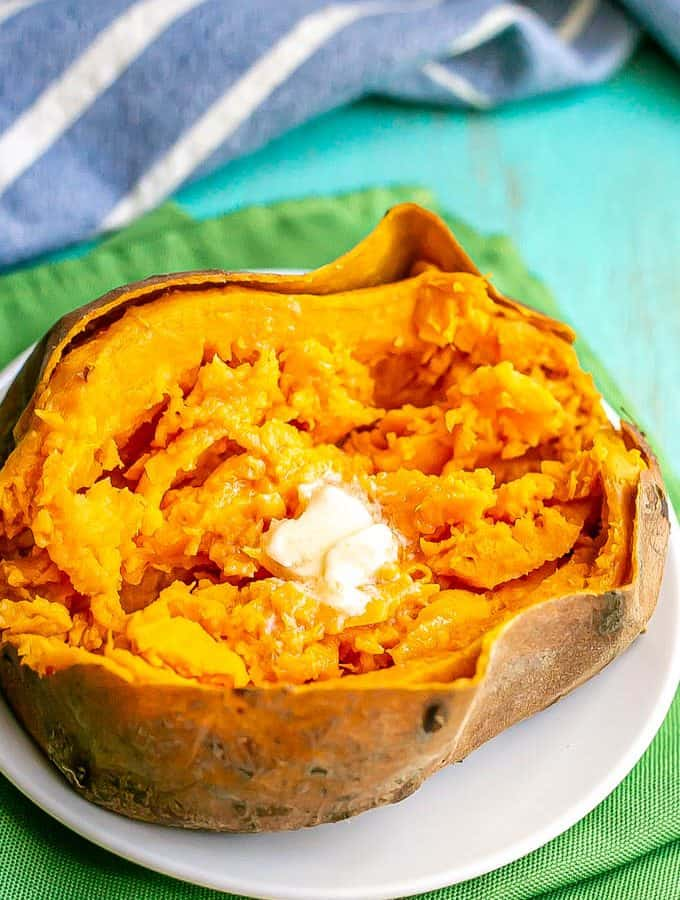 A sweet potato on a small white plate opened and fluffed and topped with a pat of butter