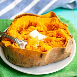 A fork resting in a cooked sweet potato with butter on top