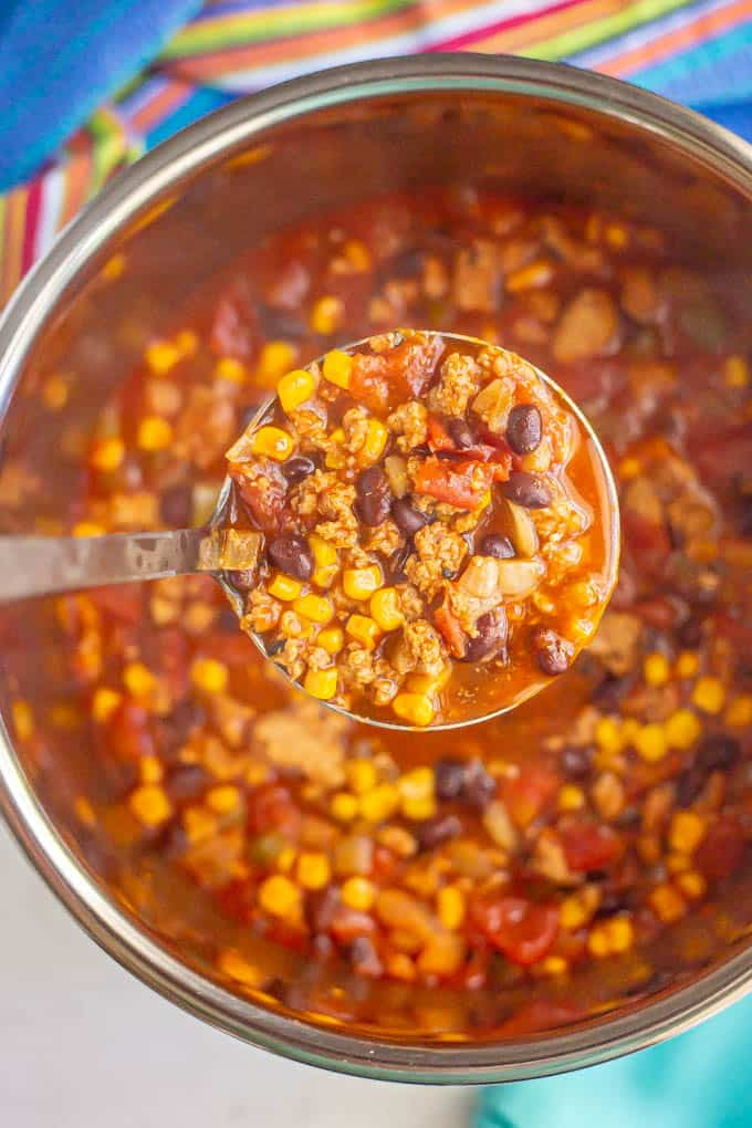 A ladle full of turkey chili with black beans and corn lifted from an Instant Pot insert