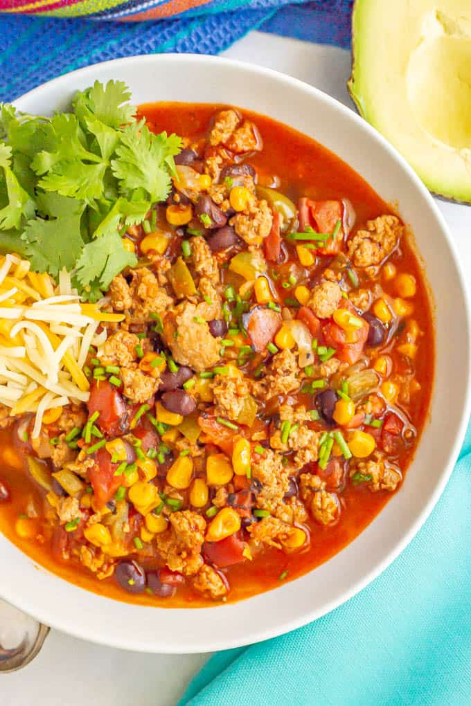 Close up of a colorful ground turkey chili in a white bowl with toppings to the side