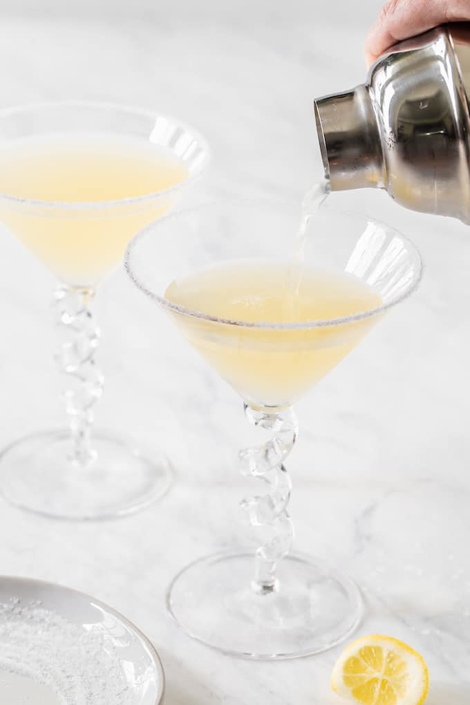 A lemony martini mixture being poured from a shaker into a martini glass