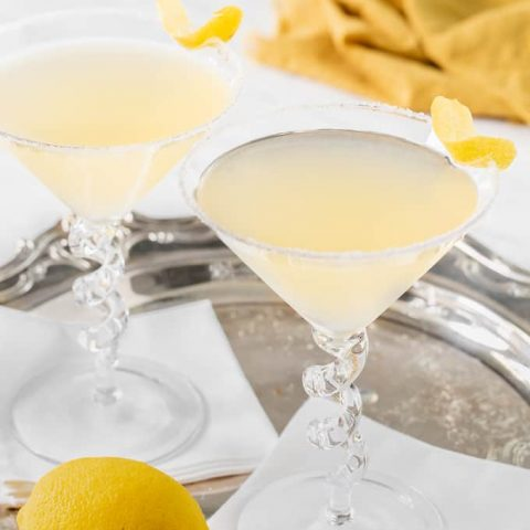 Two lemon drop martinis with lemon wedges for garnish set on white napkins in a silver serving tray