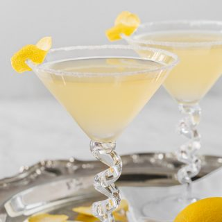 Two lemon drop martinis in glasses on a silver tray with lemon garnishes