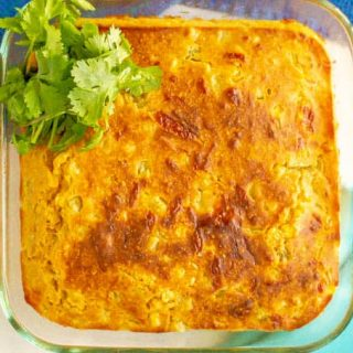 A glass dish of golden brown cheesy baked cornbread with a garnish of cilantro on the side