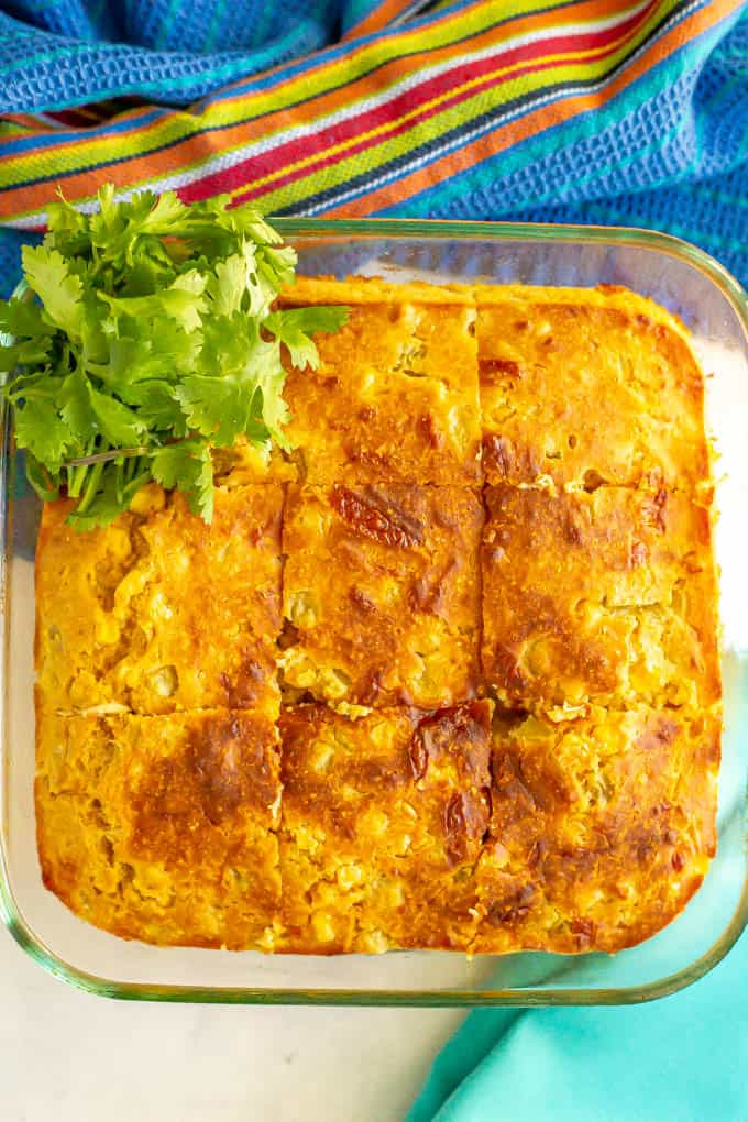 A glass dish of golden brown baked cornbread sliced into 9 squares with a garnish of cilantro on the side