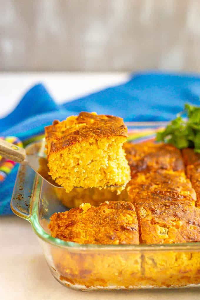 A side angle shot of a piece of Mexican style cornbread being lifted out of a baking dish