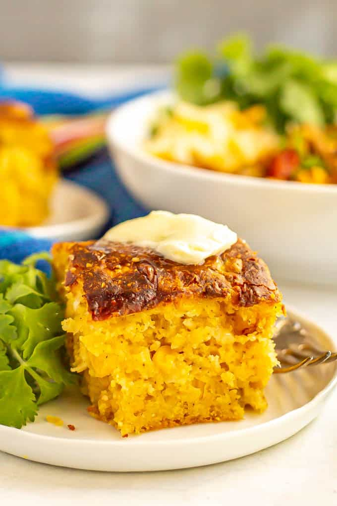 A piece of fluffy cornbread served on a small white plate with butter and a fork alongside