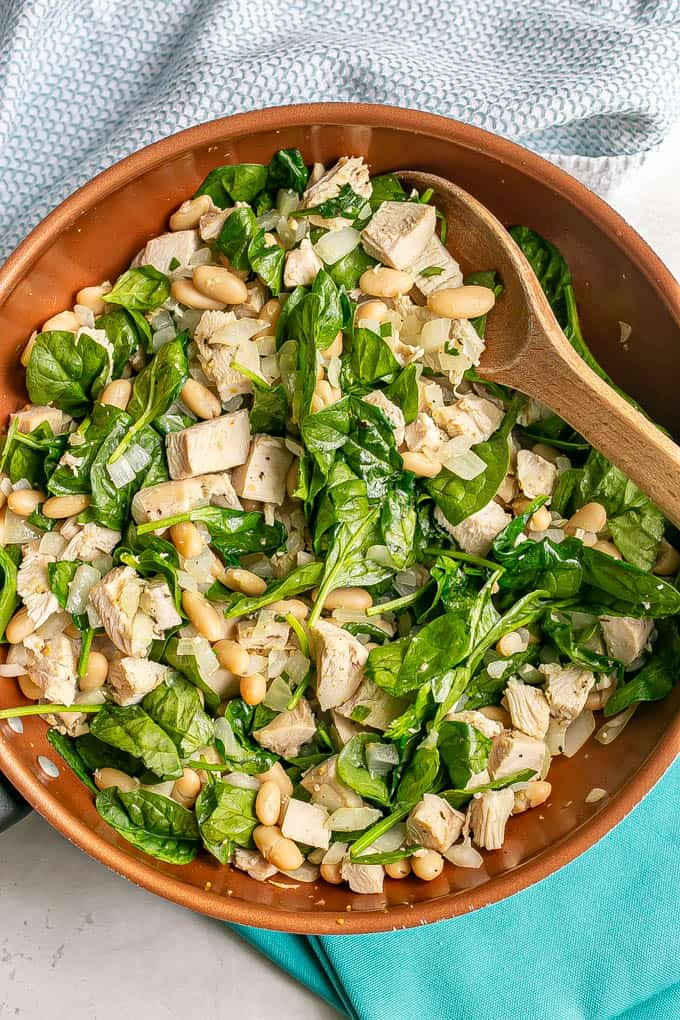A wooden spoon resting in a copper skillet with a mixture of turkey, white beans and spinach