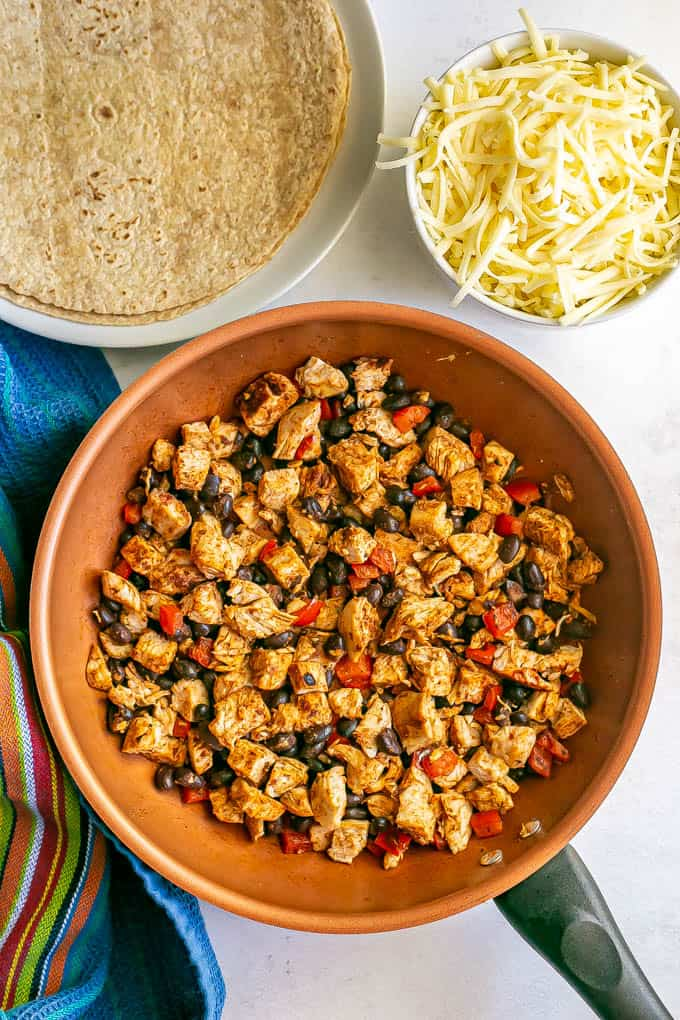 A skillet with a mixture of turkey, black beans and red pepper, plus a bowl of cheese and a plate of tortillas nearby