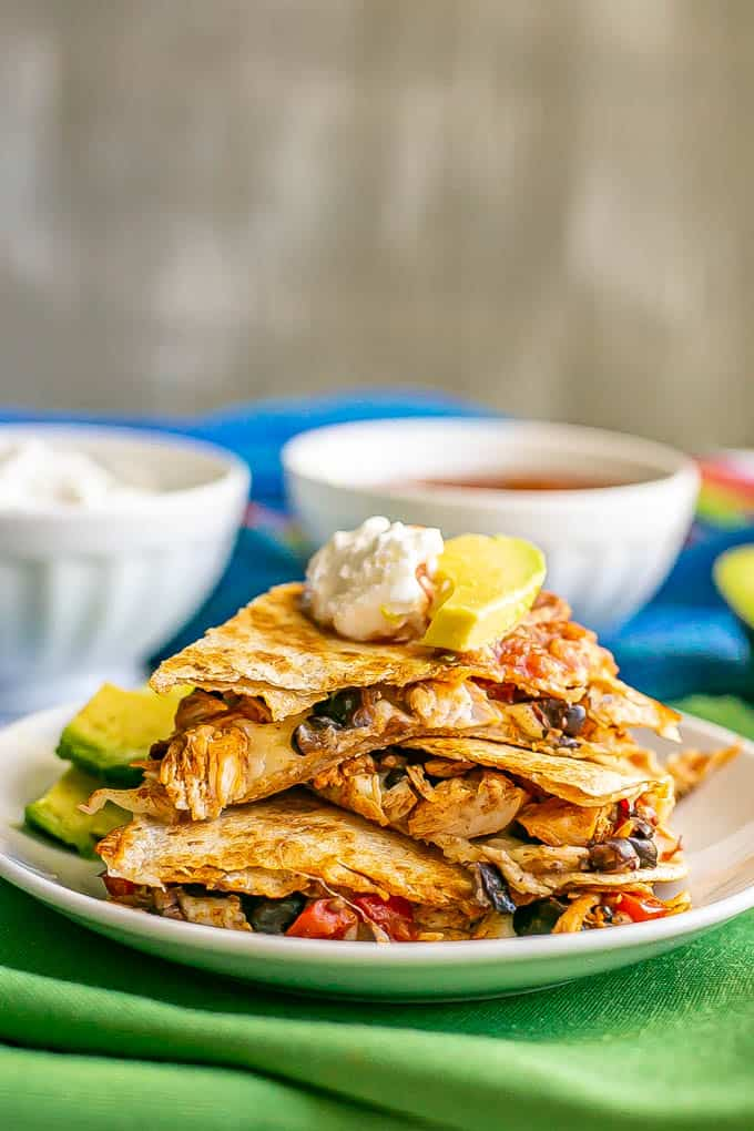 Turkey and black bean quesadillas stacked on a white plate with Greek yogurt, salsa and avocado on top