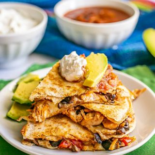 Turkey and black bean quesadillas stacked on a white plate with toppings on top and nearby