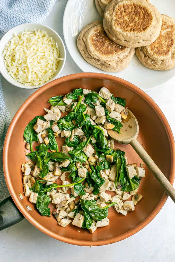 A copper skillet with turkey, spinach and mushrooms with a plate of English muffins and a bowl of mozzarella nearby