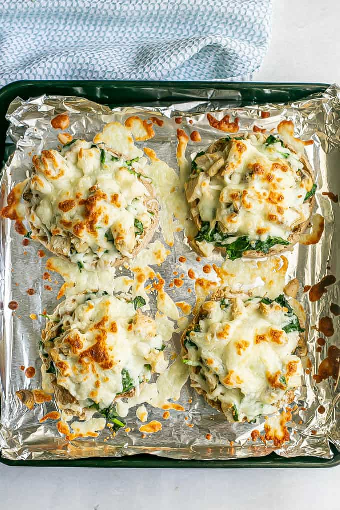 Four English muffin halves with turkey, spinach and mushrooms with melted mozzarella on top on a foil lined baking sheet