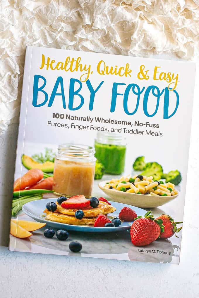 Cover of a baby food cookbook on a counter with a frilly white blanket