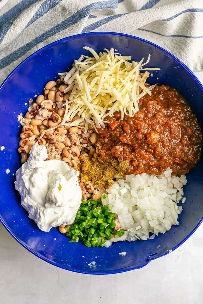 Black eyed peas, cheese, salsa and other ingredients layered in a large blue bowl before being mixed together