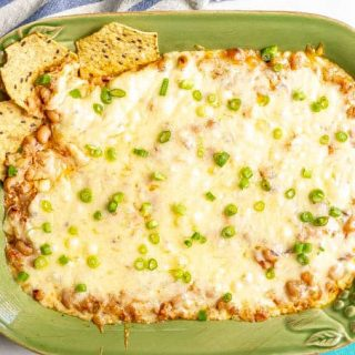 A cheesy baked black eyed pea dip in a casserole dish with green onions on top and three chips dipped in
