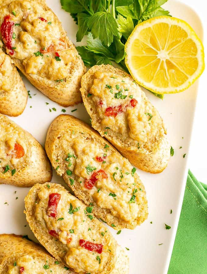Baked crab melts on toasted bread with lemon and parsley served alongside
