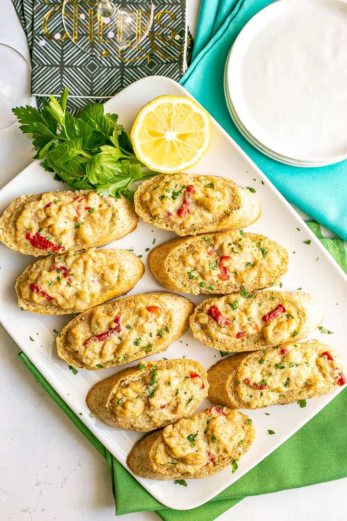 Baguette slices with a creamy crab mixture on top served on a white platter with lemon and parsley