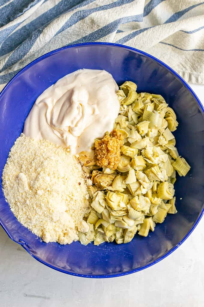 Ingredients for a creamy artichoke appetizer in a large blue bowl before being mixed together