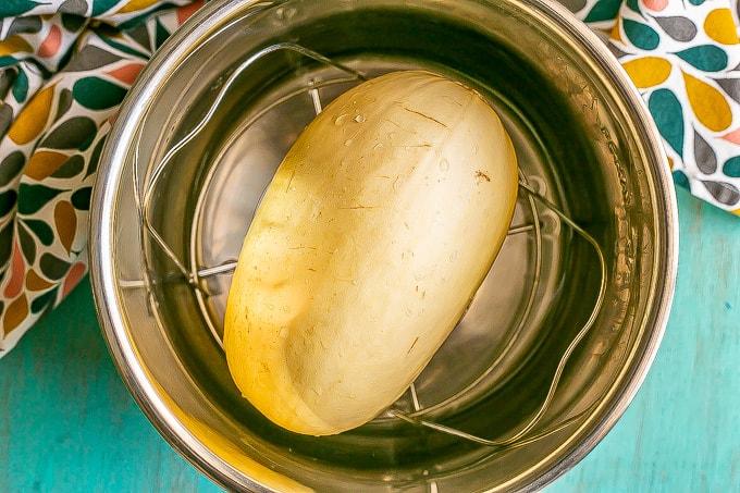 A spaghetti squash on a trivet in an Instant Pot insert