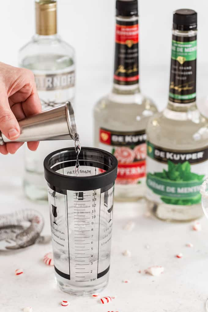 Ingredients laid out and being measured for martinis, with a shot glass being poured into a cup