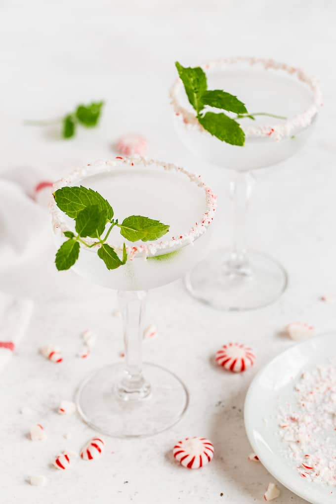 Crushed peppermint rimmed martini glasses with a clear peppermint martini and sprigs of fresh mint