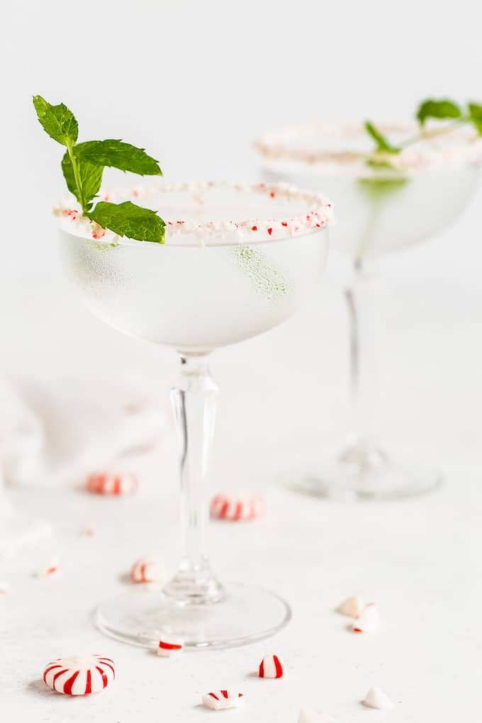 Two peppermint martinis in elegant glasses with sprigs of mint and crushed peppermints scattered