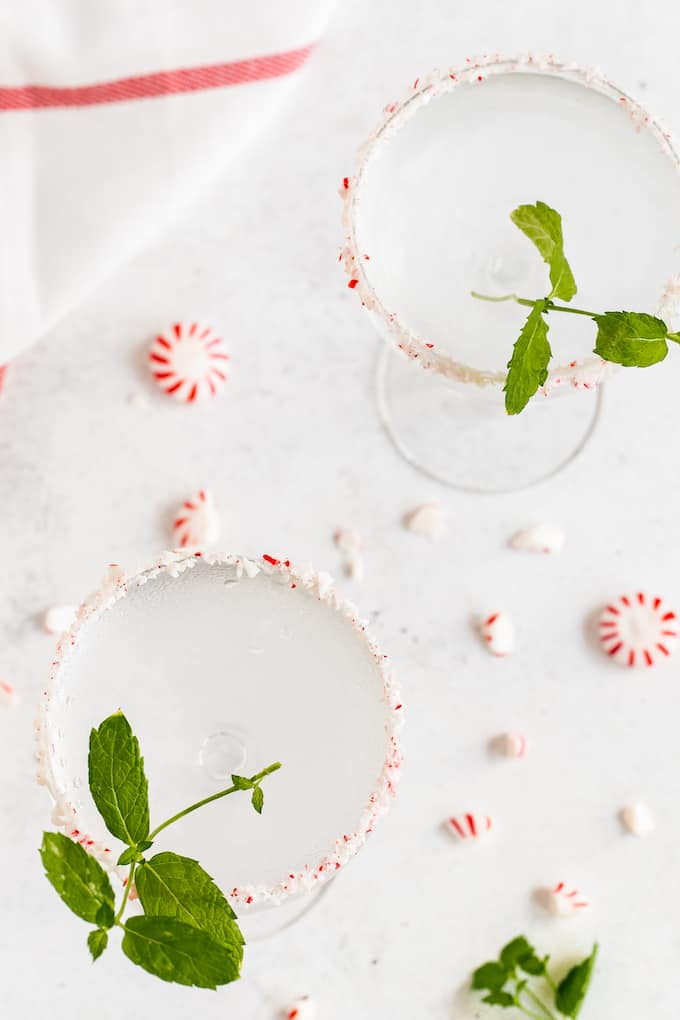 Overhead shot of two peppermint martinis with peppermint rimmed glasses, sprigs of mint and peppermint pieces scattered on the counter