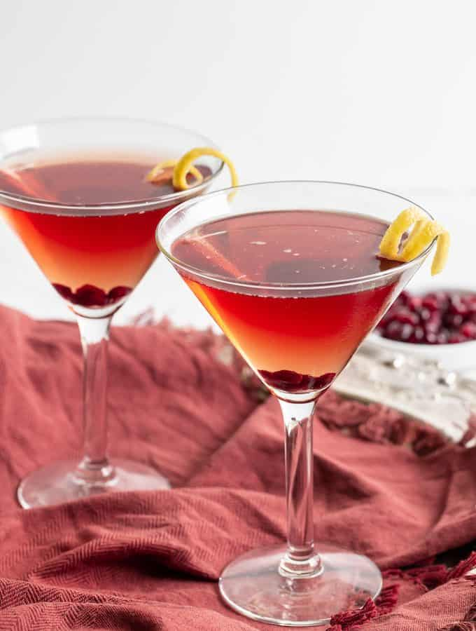 Two pomegranate martinis served in glasses with a lemon twist