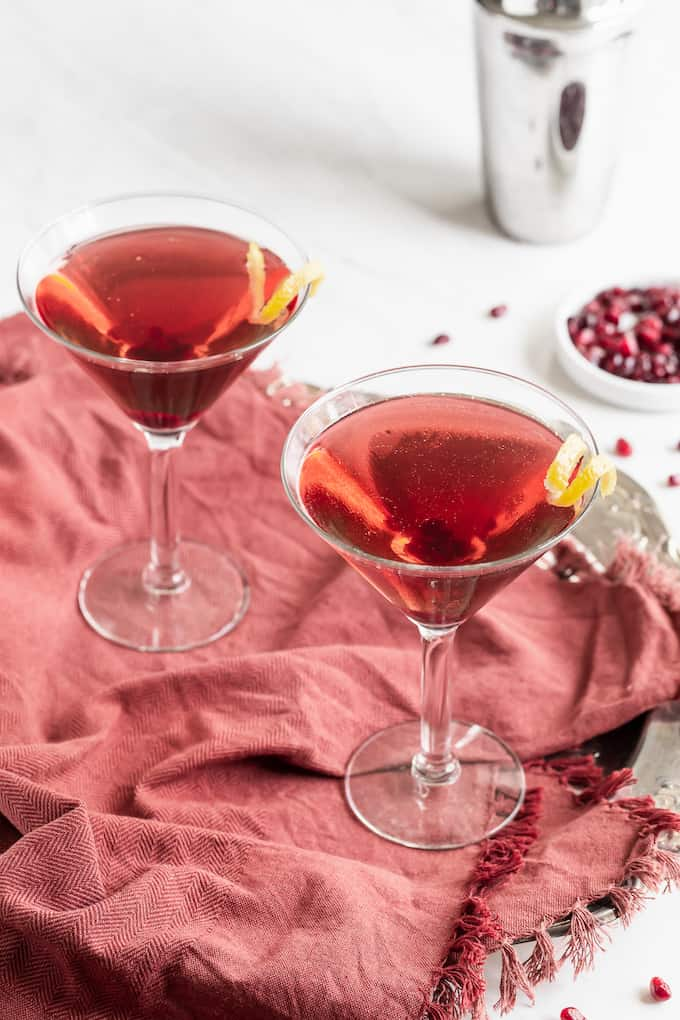 Two pomegranate martinis served in glasses with a lemon twist and pomegranate arils scattered nearby
