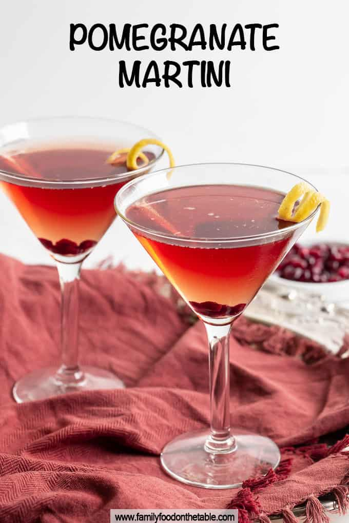 Two pomegranate martinis served in glasses with a lemon twist and a text overlay on the photo