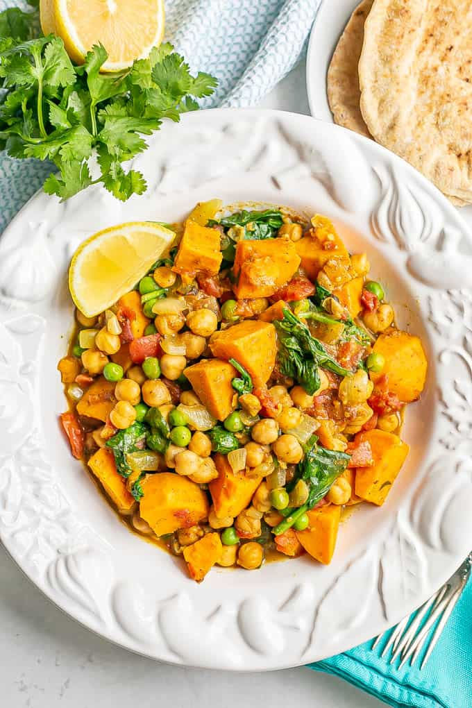 A white bowl full of a chickpea curry with sweet potatoes and spinach