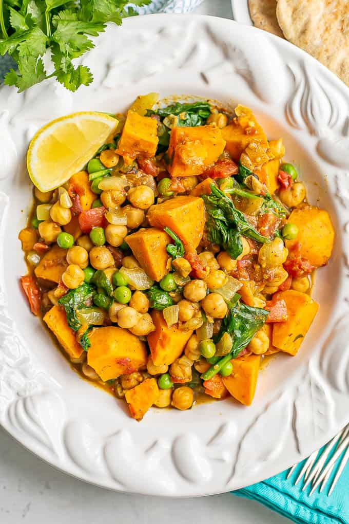 A bowl full of a chickpea and sweet potato curry with spinach and peas