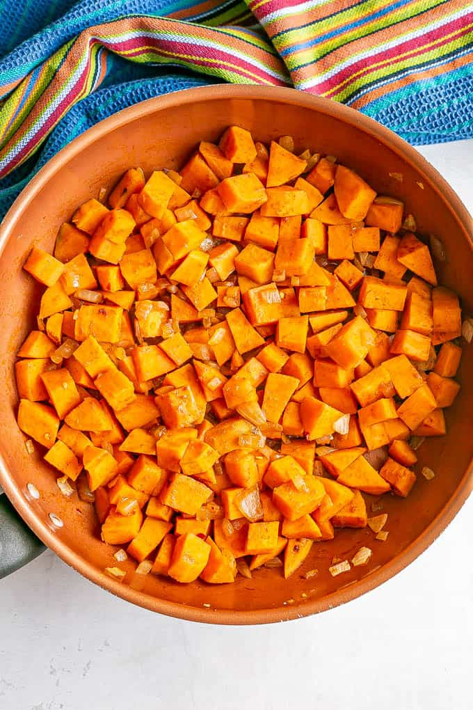Sweet potatoes cooking in a copper skillet