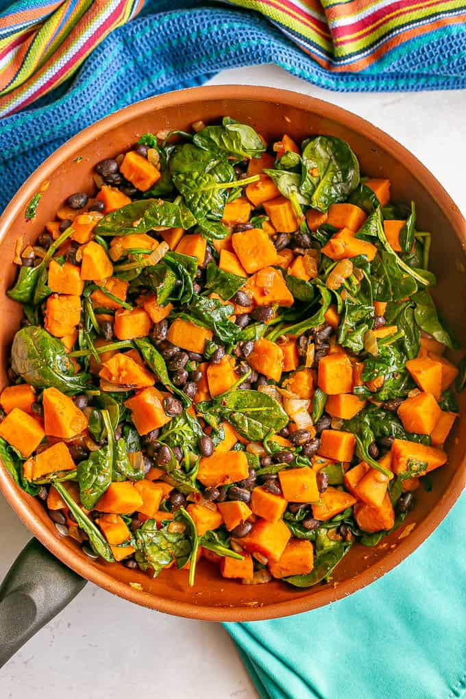 A vegetarian skillet meal with sweet potatoes and black beans and wilted spinach