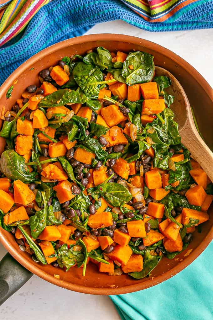 A spoon resting in a skillet of sweet potatoes with black beans and spinach