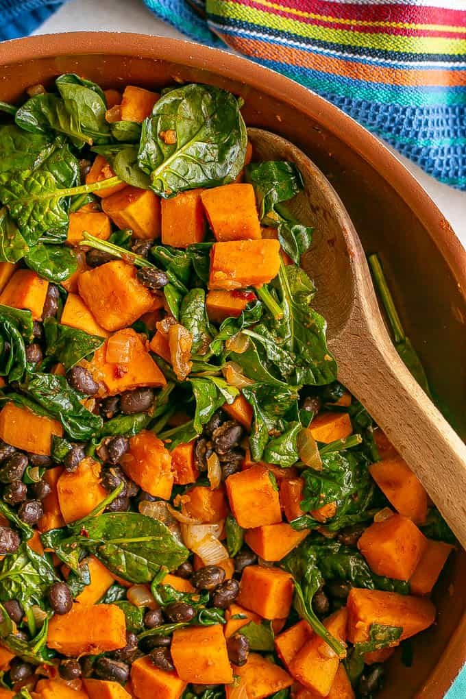 Close up of a copper skillet with sweet potatoes, black beans and wilted spinach