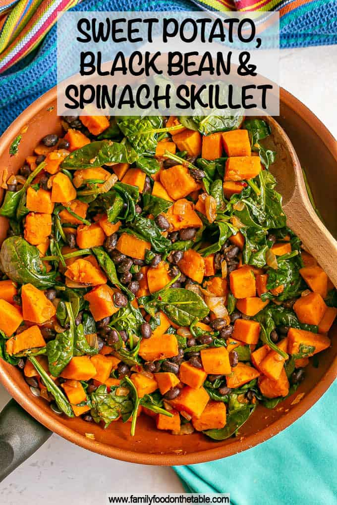 A spoon resting in a skillet of sweet potatoes with black beans and spinach with a text overlay on the photo