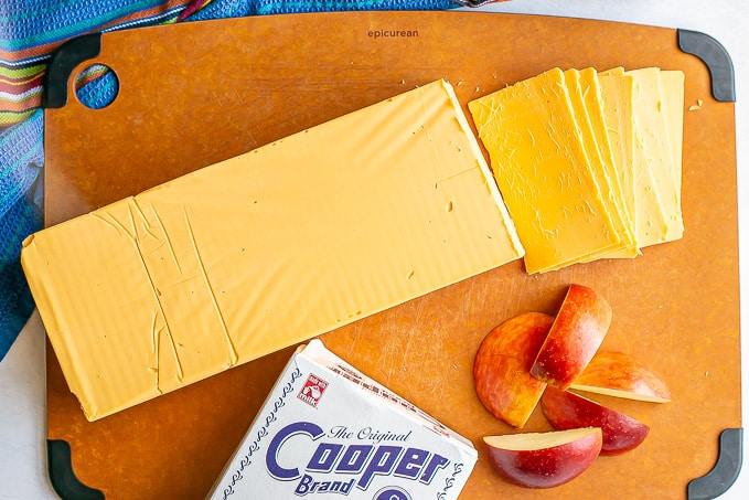 Cooper American cheese on a cutting board with some apple slices